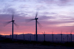 Wind power mills at sunrise Stock Images