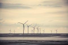 Wind power at the mud flat near sea shore. Wind turbine generating electricity at the mud flat near sea shore Stock Photos