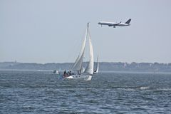 Wind Power, Plane and Sail Boat. It was perfect timing as a sail boat catches the wind and a huge airplane flew over stock photography