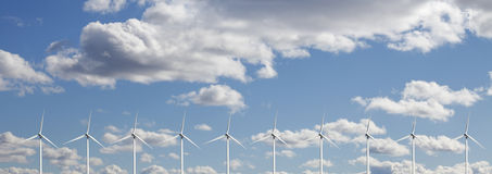 Wind-power plant against white puffy clouds. Wind-power plant set against a clear blue sky, white puffy clouds concept Royalty Free Stock Image