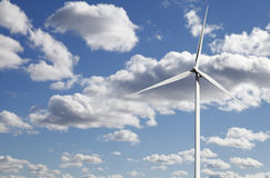 Wind-power plant against white puffy clouds. Wind-power plant set against a clear blue sky, white puffy clouds concept stock photo
