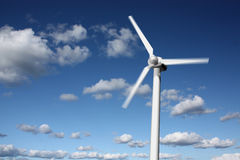 Wind power plant in motion. Wind power plant closeup with motion blur, sky and clouds in the background Stock Photo