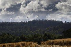 Wind-power plant in rural landscape. Wind-power plant set in old rural landscape, forest, trees, cloudy stormy sky Stock Photo
