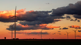 Wind power plant silhouettes in sunset Royalty Free Stock Images
