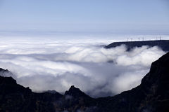 Wind power plants above clouds Royalty Free Stock Image