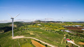 Wind power plants on a green hills aerial drone Royalty Free Stock Image