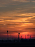 Wind power plants at sundown. With colorful clouds and sky royalty free stock image