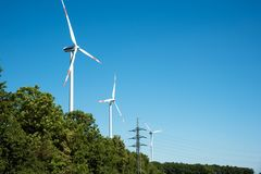 Wind power plants and trees Stock Photos