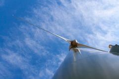 Wind turbine generator pylon. Wind power pylon from bottom next to base, against blue sky and white clouds Royalty Free Stock Photography