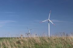 Wind power station in the daytime in the spring. Rotating blades of energy generators. Ecologically clean electricity. Modern tech. Nologies for the use of royalty free stock photo