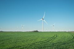 Wind power station on field. Technology and inovation. Green energy composition. Wind turbines. Industrial landscape royalty free stock photo