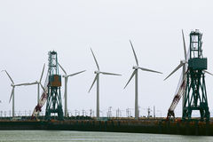 Wind power station on the pier with the port cranes Royalty Free Stock Photos