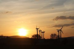 Wind power station in sunset. Romantic evening and modern technologies of ecologically clean electricity. Protection of the enviro. Nment. Bright Future. An royalty free stock photography
