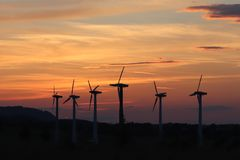 Wind power station in sunset. Romantic evening and modern technologies of ecologically clean electricity. Protection of the enviro. Nment. Bright Future. An royalty free stock image