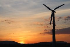 Wind power station in sunset. Romantic evening and modern technologies of ecologically clean electricity. Protection of the enviro. Nment. Bright Future. An stock photo