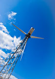 Wind power station - wind turbine against the blue Royalty Free Stock Photography