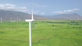 Wind power turbine on blue sky and mountain landscape drone view. Wind generator for clean renewable energy aerial view. Windmill turbine in green field stock video