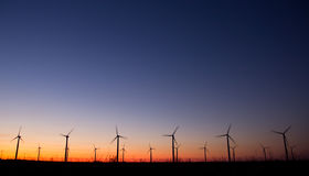 Wind power turbines. In a plant at sunset Royalty Free Stock Images