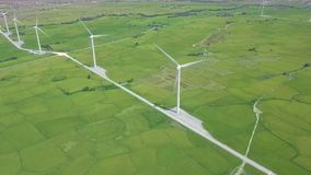 Wind power turbines on agricultural field aerial view. Wind generator on energy station on green field drone view. Windmill turbine for generation natural stock video footage