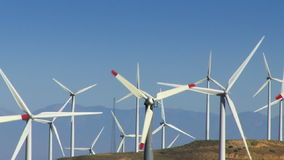 Wind Power Turbines (Alternative Energy). Spinning wind turbines on green hills and clear blue sky. Shot on HD 1080p stock video footage