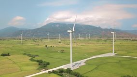 Wind power turbines generating clean renewable energy aerial view. Windmill turbine in green agricultural field on blue. Sky and mountain landscape. Drone view stock video