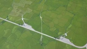 Wind power turbines on green agricultural field drone view. Wind generator on alternative energy station aerial view. Windmill turbine for generation natural stock video footage