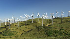 Wind Power Turbines (Green Hills & Blue Sky). Spinning wind turbines on green hills and clear blue sky. Shot on Canon HD 1080p stock footage