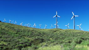 Wind Power Turbines (Green Hills & Blue Sky). Spinning wind turbines on green hills and clear blue sky. Shot on HD 1080p stock video footage