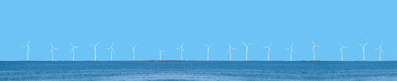 Wind power turbines. In a long horizontal line, coastal placement, with blue sky and ocean Stock Photos