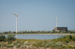 A wind-powered generator at the base of the greenery. And reservoir Stock Image