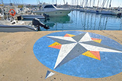 Wind rose in Alghero harbor. Wind rose painted on Alghero harbor.Boats in the background on a sunny day Stock Photos