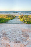 Wind rose beach. A big wind rose symbol before the walkway that lead to the beach Stock Image
