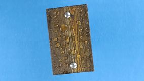Wind shakes drops of water on a rotating wooden board with iron bolts, isolated on blue. stock video