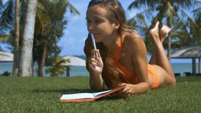 Wind Shakes Woman Long Hair Palms she Tans on Lawn. Closeup wind shakes woman long hair palm branches lady tans on grass lawn with book against beach umbrella stock video footage