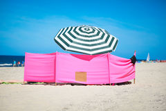 Wind shelter and parasol on the beach Royalty Free Stock Images