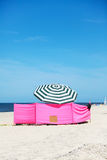 Wind shelter and parasol on the beach Royalty Free Stock Photography