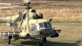 Wind shot Military helicopter landing on battlefield. Outdoor stock video footage