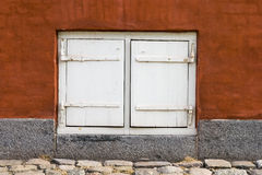 Wind shutter. White wind shutter on red wall Stock Image