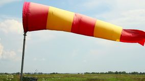 Wind sock in airport at daytime, cloudy windy weather stock video