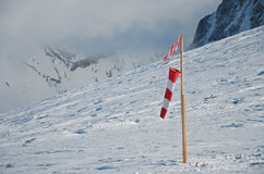Wind-sock on snow. Wind sock or wind indicator on snow. Red and white Stock Photos