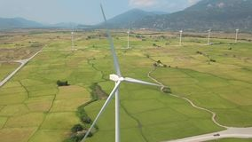 Wind station generating clean renewable energy on green field and mountain landscape. Drone view windmill turbine in. Field. Wind energy plant power turbine stock video footage