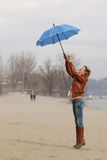 Wind steal the blue umbrella from girl Royalty Free Stock Photo