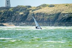 Wind Surfer Enjoys The Beach At Newborough Warren With The Island Of Llanddwyn In The Background , Isle Of Anglesey Royalty Free Stock Photography