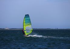 Wind surfer sail boarding across the ocean. With a green sail Stock Photos
