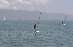 Wind surfers. On the sea with mountains in the distance stock photos