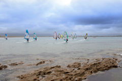 Wind surfers braving the heavy storm and rocks Royalty Free Stock Image