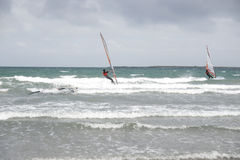 Wind surfers braving the storm winds Stock Photos