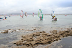 Wind surfers braving the strong storm and rocks Royalty Free Stock Photo