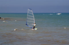 Wind surfing. A girl wind surfing along the shore on lake michigan Stock Photos
