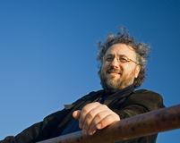 Wind swept mature man. Mature bearded man with wind swept hair against blue sky Royalty Free Stock Images